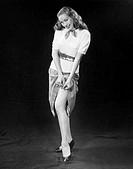 Portrait of a young woman adjusting a garter belt