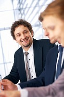 Young smiling businessman on the meeting looking and listening to partners