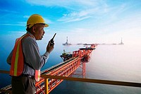 Oil rig foreman talking on a walkie_talkie