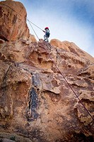 Boy rock climbing, Joshua Tree National Monument, California, USA