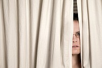 Young woman, wearing glasses, peeking out from behind two curtains