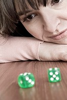 Young woman looking at a pair of green dice