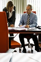 Businessman talking to female colleague as she making notes