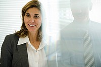 Smiling businesswoman looking away, businessman behind glass wall