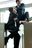Businessmen fighting to beat each other through turnstile (thumbnail)