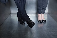 Man and woman standing in elevator, man moving foot toward woman's foot
