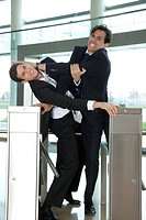 Businessmen fighting to beat each other through turnstile