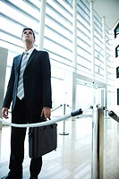 Businessman standing in lobby, looking up
