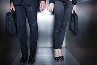 Colleagues holding hands in elevator, low section