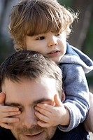 Toddler boy covering father's eyes with his hands, portrait