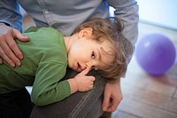 Toddler boy resting head on father's lap
