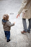 Father reaching for toddler's hand on sidewalk, cropped