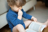 Toddler boy looking at book