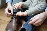 Chhild helping father tie shoelace (thumbnail)