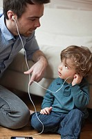 Father and toddler son listening to MP3 player with earphones, portrait