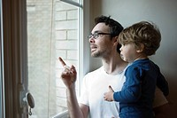 Father and toddler son looking out window together