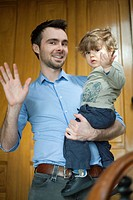 Father and toddler son waving at camera