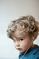 Toddler boy wearing earphones, portrait