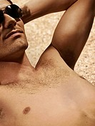 Bare_chested man sunbathing on beach