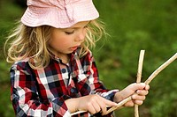Girl playing with sticks outdoors
