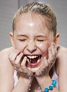 Laughing girl washing her face