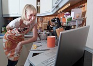 Woman using laptop to cook in kitchen