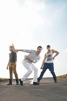 Men dancing in road