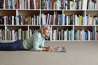 Older woman reading by bookshelves
