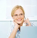 Young Woman in office using telephone, smiling
