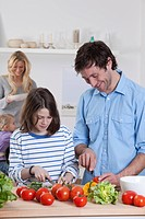 Germany, Bavaria, Munich, Son preparing salad with father, mother and daughter in background