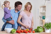Germany, Bavaria, Munich, Mother preparing salad with father and daughter standing beside her
