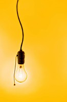 Incandescent lightbulb on yellow background