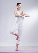 Mid adult woman in tree pose against white background