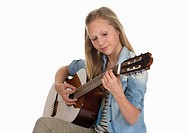 Girl playing guitar against white background