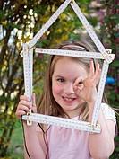 Close up of girl holding house shape made up of folding ruler, smiling, portrait