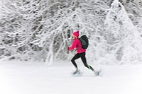 A woman snow shoeing through a snowy winter landscape