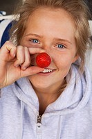 Portrait of blond teenage girl eating strawberries