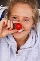 Portrait of blond teenage girl eating strawberries