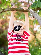 Boy wearing eye patch hanging from branch of tree