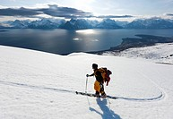 Man skiing uphill, lake and mountain in background