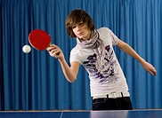 Teenage boy playing table tennis