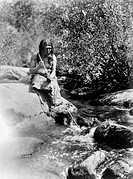 CALIFORNIA: MIWOK MAN, c1924.A Miwok man holding a fishing spear, seated on a boulder in a creek in California. Photograph by Edward Curtis, c1924.