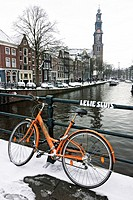 Bicycle parked on snow covered bridge over Prinsengracht in Amsterdam
