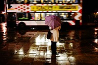 Scotland, City of Edinburgh, Edinburgh. A woman standing under an umbrella on Princes Street waiting for someone