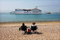 England, Hampshire, Portsmouth. A couple relaxing in portable chairs on the beach watching a ferry leave the port of Southsea