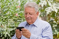 Senior Chilean man text messaging on cell phone