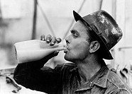 TEXAS: OIL WORKER, 1939.An oil field worker drinking a bottle of milk during lunch at Kilgore, Texas. Photograph by Russell Lee, April 1939.