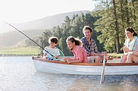 Family fishing in boat on lake