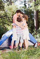 Family hugging outside tent