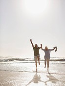 Senior couple jumping on beach